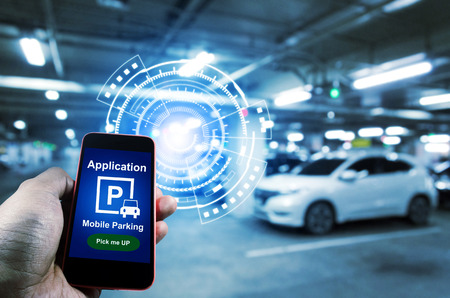 Pick me up, mobile smart phone in hand using application for intelligent car park with digital hologram on blurred parking car background, mobile auto parking, network and online technology concept Stock Photo