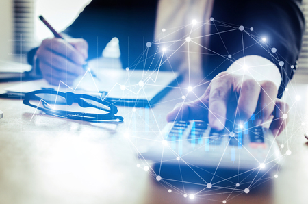 professional investor or business man analysis and calculating on financial reports on desk in office with graphic graph chart of stock market investment trading, financial and technology concept