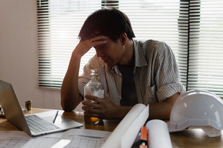 young asian engineer, architect, contractor thinking and worrying about new project contract plan with laptop and bottle of alcohol on desk in office center at construction site, alcoholism concept Stock Photo