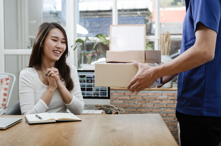 home delivery service man in blue uniform and young woman customer appending signature in digital mobile phone receiving parcel post box from courier at home, express delivery, online shopping concept
