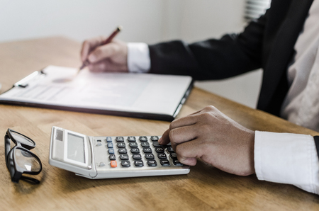 professional investor or accountant analysis and calculating on financial reports and using calculator on desk in office, investment, financial adviser, business working and saving money concept