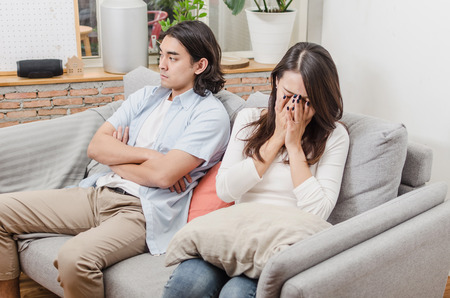 sadness young asian wife having quarrel and sitting on sofa after fight with husband behind her in house interior together, upset couple, love, divorce couple, family issues and relationship concept