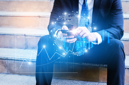 business man in modern black suit using mobile smart phone sitting on walkway in city with effect global world map network link connection and graph chart, investor, technology communication concept