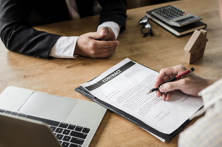 Realtor - young man customer signing contract for buying house with real estate broker in suit at estate agent office, investment, home loan contract, buy and sell home, real estate, insurance concept