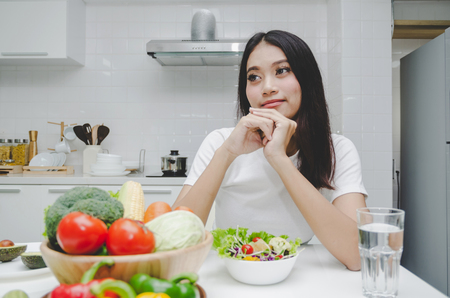 beautiful young asian woman slim body in white shirt dieting and eating healthy food, fresh vegetable salad sitting in kitchen interior in house, lifestyle, good healthy, diet food and drink concept