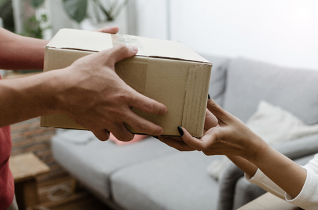 close up hand of home delivery service man in uniform handing parcel boxes to recipient and young customer accepting parcel post box from courier at home, express delivery and online shopping concept