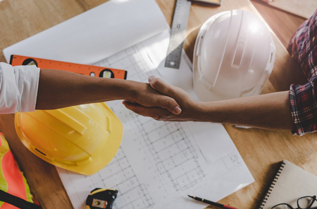 top view construction worker team contractor hand shake after finishing up business meeting to greeting start up project contract in construction site building, teamwork, partnership, industry concept Stock Photo