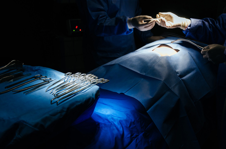 surgical instrument lying on table while group of surgeon performing work in operation room at hospital, emergency case, surgery, medical technology, health care cancer and disease treatment concept Stock Photo