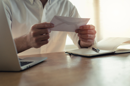 happy young employee business man holding money bonus card in paper envelope to increasing of salary or promotion new position in office, resignation letter, losing job, fired from job concept Stock Photo