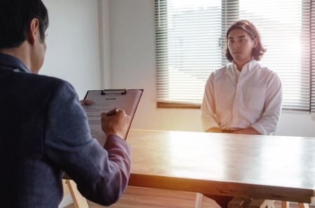 young attractive man during job interview and explaining about his profile with business HR manager holding resume and sitting in meeting room at office, business job interview and employment concept
