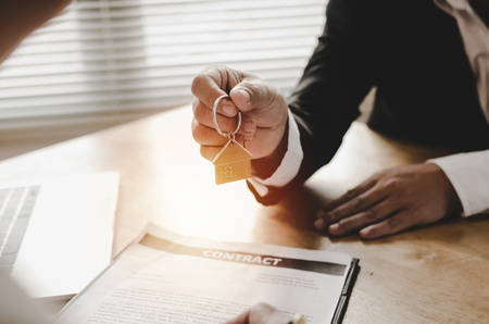 real estate broker manager giving house key to customer after signing contract for buying house in estate agent office, investment, home loan contract, selling house, realtor and real estate concept