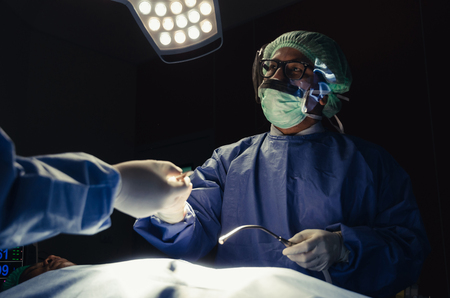 Doctor and Assistant surgeon sending surgical instrument to hand work for rescue patient in operation room at hospital, emergency case, surgery, medical technology, health care cancer, disease concept