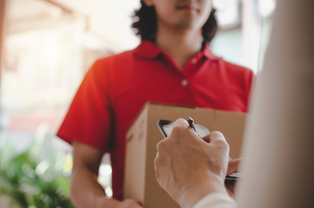 young woman customer appending signature in digital mobile phone receiving parcel post box from courier with home delivery service man in red uniform at home, express delivery, online shopping concept Banco de Imagens