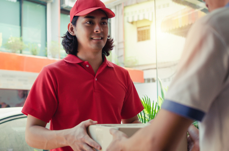 smart home delivery service man in red uniform handing parcel boxes to recipient and young man customer accepting parcel post box from courier at home, express delivery and online shopping concept