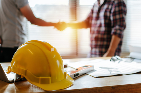 yellow safety helmet on workplace desk with construction worker team hands shaking greeting start up plan new project contract in office center at construction site, partnership and contractor concept Standard-Bild