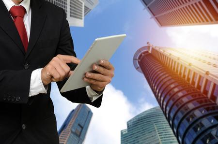 Junger gutaussehender Geschäftsmann im Anzug liest Informationen über Finanznachrichten mit mobilem Tablet mit Sonnenaufgang und Stadtbildhintergrund, Netzwerktechnologie, Finanzinvestitionen, Partnerschaftskonzept Standard-Bild