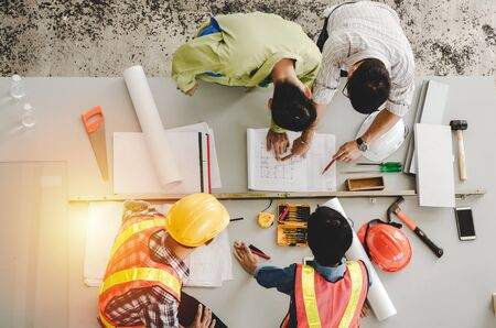 top view of group of engineer, technician and architect planning about building plan with blueprint and construction tools on the conference table at construction site, contractor and teamwork concept