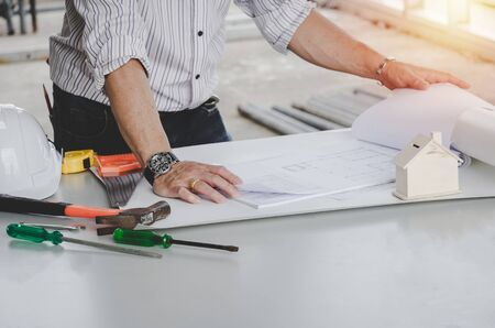 professional architect, engineer or interior drawing with blueprint and tools on conference table in office center at construction site, contractor, construction, engineering and home design concept