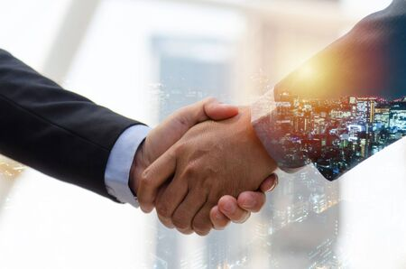 Welcome. double exposure image of investor business man shaking hands with partner for successful meeting deal with during sunrise and cityscape background, investment, partnership, teamwork concept 免版税图像