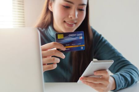 young pretty woman entering security code with mobile phone and paying credit card on desk at home office, internet network technology, electronic online booking, payment and shopping online concept Stock Photo - 129903081