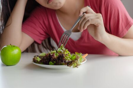 Diet. asian young pretty woman bored emotion and refuse for eating fresh green vegetables salad on table for good health at home, nutrition, weight loss, lifestyle, healthy food and dieting concept Stock Photo