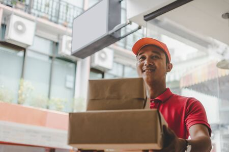 asian young delivery service man in red uniform sending parcel post box to customer at home, cargo shipping, express delivery service, online shopping, service occupation and logistics concept