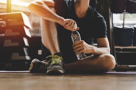 Musculoso joven guapo caucásico tomando un descanso relajarse y beber agua mientras descansa después del entrenamiento para una buena salud en el gimnasio por la mañana, culturista, estilo de vida y concepto de ejercicio deportivo Foto de archivo