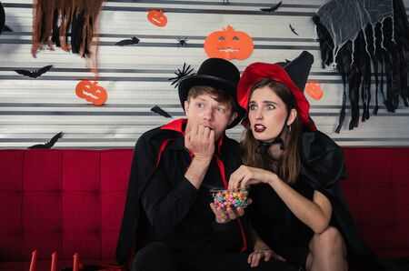 Halloween. young scared caucasian couple in vampires and witch clothing enjoying watching horror movie in television and sitting on sofa in halloween party at home, holiday, halloween festival concept 写真素材