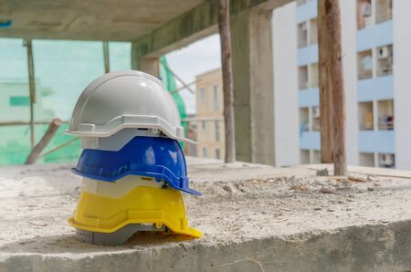 white, yellow and blue hard safety helmet for safety accident stack on floor at workplace in construction site building background, safety first, contractor business, industry and construction concept
