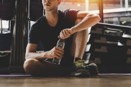 muscular caucasian young handsome man taking a break relax and drinking water while resting after workout for good healthy in fitness gym at morning, bodybuilder, lifestyle and sport exercise concept