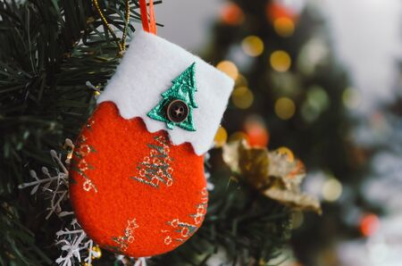 Merry Christmas. red color decorated sock hanging on christmas tree with bokeh light background, holiday family, happy new year and merry christmas festival concept, vintage color tone effect