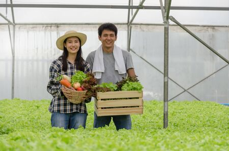 asian young friendly couple farmer smiling and holding organic hydroponic fresh green vegetables produce wooden box together in greenhouse garden nursery farm, business farmer and healthy food concept 版權商用圖片