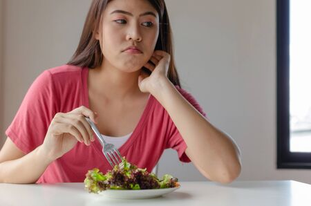 Diät. asiatische junge hübsche frau langweilte sich und weigerte sich, frischen grünen gemüsesalat auf dem tisch für gute gesundheit zu hause, ernährung, gewichtsverlust, lebensstil, gesundes essen und ernährungskonzept zu essen