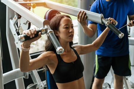 muscular young sporty woman exercising chest press machine with personal trainer for perfect body in fitness gym, bodybuilder, healthy lifestyle, exercise fitness, workout and sport training concept