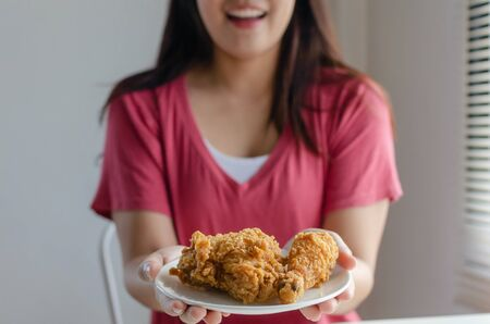 Asian young pretty woman slim body smiling and holding delicious crispy fried chicken on dish in kitchen at home office, junk food, unhealthy food, dieting, weight loss and good healthy concept 版權商用圖片