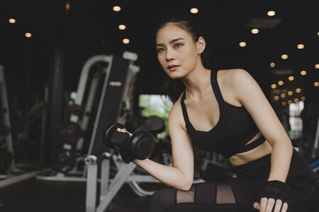 athletic young asian pretty slim body woman exercise with dumbbell in fitness gym with machine in background, bodybuilder, healthy lifestyle, exercise fitness, workout and sport training concept Reklamní fotografie