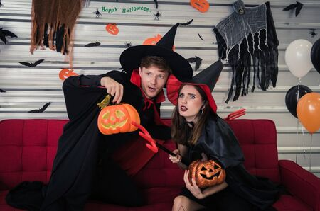 Halloween. couple young caucasian man and woman in vampires and witch clothing holding pumpkin head lantern and sitting on sofa in halloween party at home, holiday and halloween festival concept