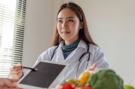 Food science. beautiful friendly nutritionist female doctor medical with tablet talking about diet plan with vegetable to young patient in office hospital, nutrition, nutritional, healthy food concept