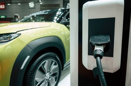 EV Tech. power supply connect station for electric vehicle battery charge for future, electric car, technology transport industry, hybrid car, power saving, global warming and automobile concept