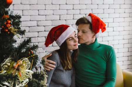 young caucasian sweet couple with red santa hat enjoy and kissing his girlfriend on sofa with christmas tree celebrating in house, holiday family, happy new year and merry christmas festival concept 스톡 콘텐츠