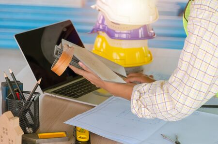 professional architect, engineer or interior design choosing about material veneer wood sample with laptop and safety helmet on workplace desk in office center at construction site, contractor concept