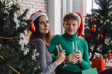 aucasian sweet couple with red santa hat enjoy drinking champagne and looking at camera with christmas tree celebrating in house, holiday family, happy new year and merry christmas festival concept Banque d'images - 131854543