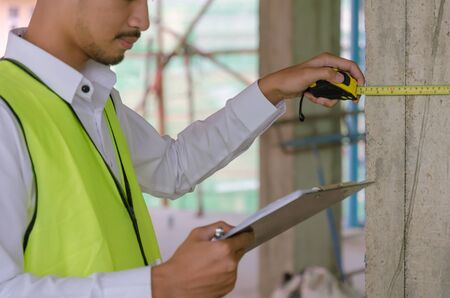Inspection. young foreman builder, engineer or inspector checking and inspecting with clipboard and measuring tape at construction site building interior project, contractor and engineering concept