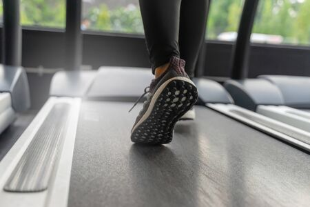 Run. motion runner woman feet running on machine treadmill at fitness gym center or health club with sunlight effect, cardio, healthy lifestyle, exercise fitness, workout, sport training concept