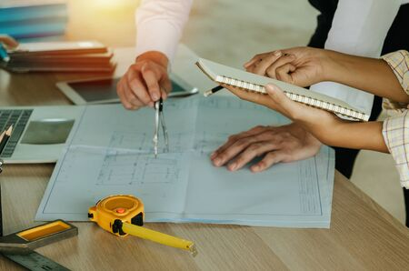 construction worker team meeting and planning about building plan with blueprint, construction tools on conference table at construction site, contractor, business, industry and construction concept