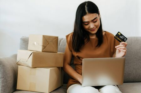 asian young pretty woman showing credit card and working with laptop computer and packing cardboard parcel box for send order to customer at home office, digital payment, shopping online concept Stock Photo