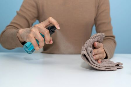 hand of woman cleaning desk with alcohol spray for clean corona virus (covid19) prevention at home office, cleaning house, health care, virus outbreak protection, self quarantine and stay home concept 版權商用圖片