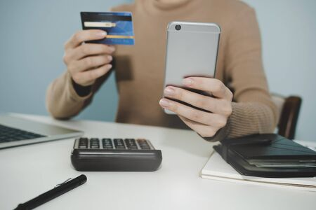 woman entering security code with digital mobile phone and paying with mock up credit card and laptop computer on desk at home office, shopping online, electronic pay and digital technology concept