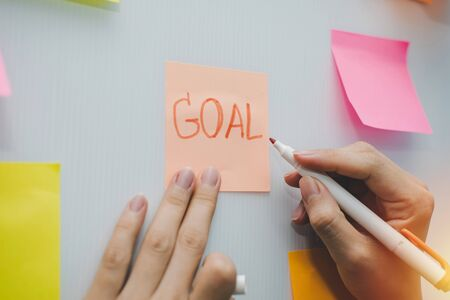 Goal. business woman hand writing with colored sheets sticky note paper on white board background in home office, business meeting, brainstorming, creative, digital online marketing, financial concept 版權商用圖片