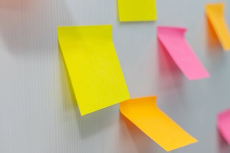 many blank colored sheets sticky note paper on white board background in home office, business meeting, brainstorming, creative idea, digital online marketing and business financial concept